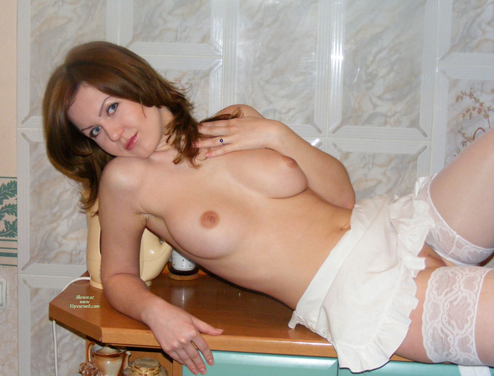 White French Maid's Apron - Blue Eyes, Brunette Hair, Shaved Pussy , Reclining On A Table, Eyes Looking At You, Soft Shoulder Length Brunette Hair, Big Blue Eyes, White Apron, White Garterless Stockings, Eyes Wide Open, Perky Round Breasts, White Lace Top Stockings