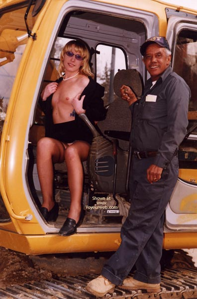 Pic #1 - Topless Equipment Operator , Topless Equipment Operator, Blonde With Sunglasses Pearl Necklace, Blonde Sitting In Tractor With Top Open, Tractor Operator Next To Topless Blonde