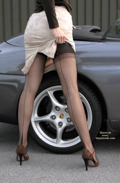 Pic #1 - Girl Standing In Front Of A Porsche - Long Legs, Rear View, Stockings , Girl Standing In Front Of A Porsche, Showing Her Long Legs, Lifting Her Skirt, Black Stockings, Brown High Heels, Rear Shot, White Skirt, Leg And Tire, Back Seam Stockings, Standing Beside A Car