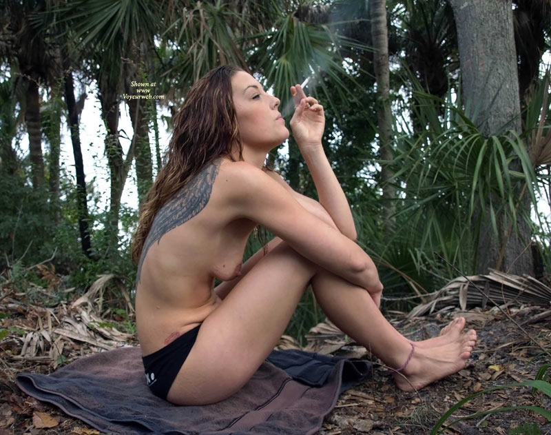 Pic #1 - Tatooed Topless Girl Smoking - Long Hair, Topless , Smoking On The Beach, Sitting With Toes Up, Sitting On Ground, Outside Topless Smoking, Small Titties, Rugged Feet, Tatooed Girl Smoking In The Woods, Sitting On The Ground