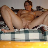 Girl Sitting On Couch Legs Spread Hand Over Pussy - Big Tits, Navel Piercing, Red Hair, Spread Legs