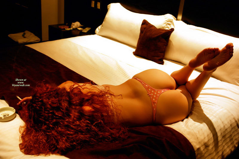 Pic #1 - Smoke-in Redhead On Bed - Long Hair, Red Hair , Red Curly Hair, Victorias Secret White Polka Dotted Thong, Bronze Colored Skin, Long Curly Hair, Sole Of Feet, Back View, Cute Ass, Barefeet, Butt Floss