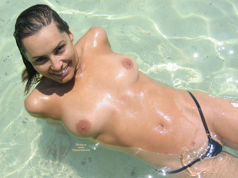 Pic #1 - Topless Laying Back In The Surf - Black Hair, Brown Hair, Topless , Black Pussy Thong, Medium Length Brown Hair, Beach Shot, Black G String, Medium Breasts, Nice Smile, Devlish Smile, Topless Laying In Shallow Water, Black Micro Thong, Topless Girl At Beach