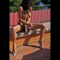 alejandra: naked brunette outside on bench with champagne