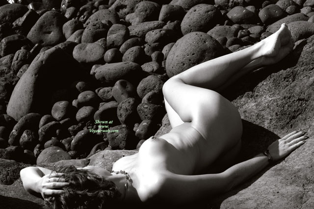 Pic #1 - Nude Model Laying Prone On Rocks - Naked Girl, Nude Amateur , Black And White Photo, Puffy Areolas, Artistic Implied Nude, Curvy Feminine Hips, Photo Taken From Above And Slightly Behind The Model, Round And Firm, Artistic On The Rocks, Left Naked On The Rocks, Legs Are Slightly Bent And Turned Away From Camera
