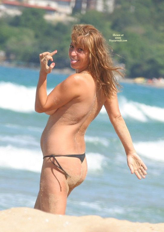 Pic #1 - Topless Girl In Thong At The Beach Flipping The Bird And Sticking Her Tongue Out - Brown Hair, Long Hair, Topless, Naked Girl, Nude Amateur , Side View Of Boob, Long Brown Hair At The Beach, Tongue Sticking Out, Nude Beach Girls, Flipping The Bird Topless, Black Thong Bikini Bottoms Only