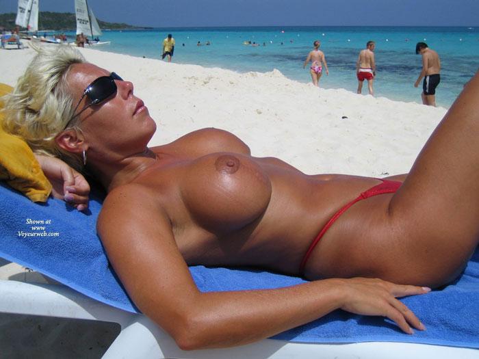 Pic #1 - Blonde On Beach Topless In Red Bikini Bottoms - Blonde Hair, Sunglasses, Topless, Beach Voyeur , Dark Sunglasses, Red Thong, Blonde Sunbathing, Red Bikini Bottom, Platinum Blonde Hair, Large Round Tits, Lying On Back At Beach, Topless Sunbathing