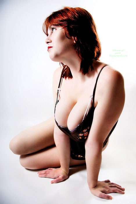 Pic #1 - Cleavage - Large Breasts, Milf, Red Hair , Large Handful Of Breasts, Black Vinyl Corsette, Black Corsett, Looking Into Distance, Red Lips, Low Cut Top, Milf Shot Against A White Backdrop, Black Bodysuit