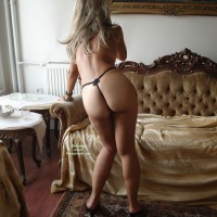 Girl In G-string, Standing With Naked Buttocks Facing Photographer - Blonde Hair, Long Hair, Round Ass