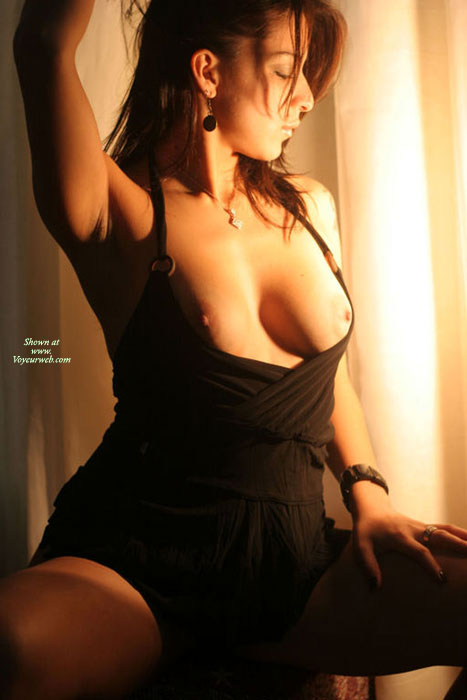 Pic #1 - Pose In Black With Amber Warm Light - Black Hair, Dark Hair, Long Hair, Topless , Top Down, Breasts Exposed, Great Sexuality, Sexy Dark, Semi-topless, Arm Raised, Black Dress Exposing Breats, Large Smooth Aerolas, Black Halter Dress