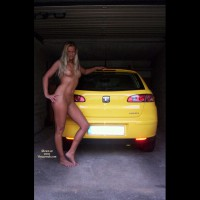 Yve: outdoor blonde wide shot leaning on car in garage