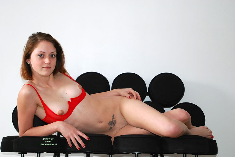 Pic #1 - Red Cupless Bra - Brunette Hair, Shaved Pussy, Small Tits, Small Areolas , Just In A Quarter Cup Red Bra, Red Fingernails, Crossed Legs, Tummy Tattoo, Slim Body, Artistic On Couch, Small Round Areolas, Red Bra