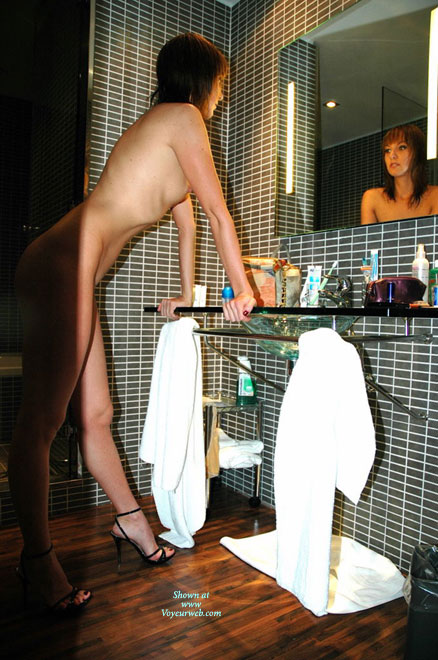 Pic #1 - Beauty In A Bathroom - Heels , Looking In Mirror, Leaning On Hands, Leaning On Counter, Black Spike Heels, Admiring Her Reflection In Heels, Red Toenail Polish, Reflection In The Mirror, Bathroom Mirror, Standing Leaning On The Sink