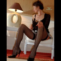 Fishnet Stockings, Black High Heels, Black Shirt Sitting In Chair - Dark Hair, Heels, Stockings