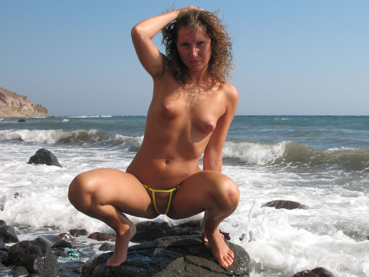 Pic #1 - Topless Squatting On Rocks In The Surf - Perky Tits, Small Tits, Topless, Looking At The Camera , Yellow G-string On The Rocks, Small Perky Tits With Yellow G-string, Firm Body, Blond Lady Next To The Sea., Legs Open, Micro Bikini, Hand On Head, Blond Lady Squatting On A Rock, Wicked Weasel, Ocean Queen, Yellow Open G-string, Crouching On Rocks, Puffy Nipples, Beach Photo