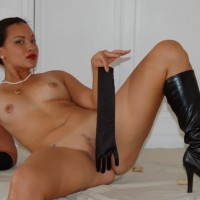 Saucy: exotic looking girl reclining naked with long gloves and knee high boots