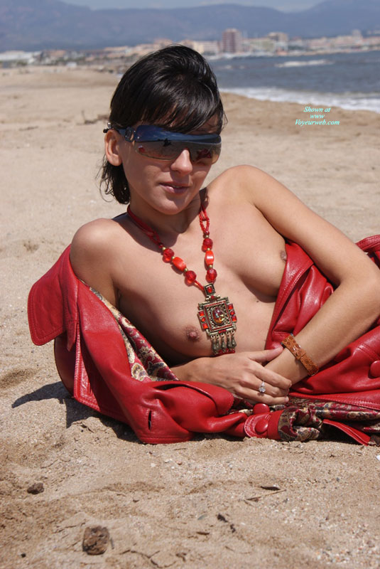 Pic #1 - Topless On Beach With Ethnic Jewellery - Flashing, Sunglasses, Topless , Wrap Around Sunglasses, Brown Leather Wrist Watch Band, Paisley Lined Red Leather Coat, Big Red Necklace, Lying On The Beach, Mirror Sunglasses, Petite Breasts, Flashing Tits, Diamond Ring