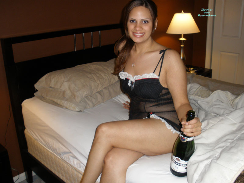Pic #1 - Latina On Bed With Wine - Brunette Hair, Looking At The Camera , Waiting On A Bed, Smiling Into Cam, Drunk Girl Ready To Be Taken Advantage Of, Black Teddy With White Trim, Legs Crossed, Brunette Hair, Negligee And Champagne, Dressed For Sex, Sitting On A Bed