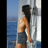 Outdoor Topless Brunette Sailing Leaning On Mast In Mini Skirt - Brunette Hair, Sunglasses, Topless