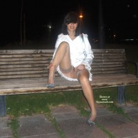 pinky: brunette sitting on bench in white dress and no panties