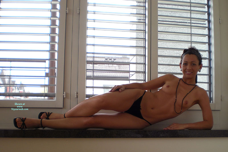 Pic #1 - Topless By The Window - Brown Hair, Long Hair, Long Legs, Small Breasts, Small Tits, Topless, Small Areolas , Black Necklace, Black Strappy Heels, Lean Body, Black Ankle Wrap Sandals, Little Tits, Black Panties