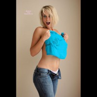 Topless Blonde In Jeans With Big Breasts - Blonde Hair, Tan Lines, Topless , White Panties Peek Above Front Of Jeans, Half Dressed, No Tan Lines, Blue Denim Jeans, Holding Teal T-shirt, Covering Tits With Teeshirt, Caught Naked!, White Cotton Panties, Surprised Look As Getting Undressed