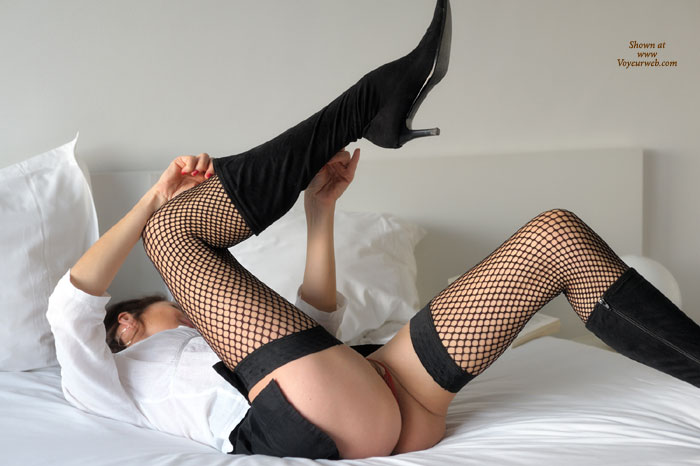 Pic #1 - Brunette In White Shirt, Black Fishnets And Calf-length Boots Undressing On Bed - Brunette Hair, Long Legs, Stockings , Long Legs In Fishnets And Boots, Large Ring Earring, White Blouse, Long Wrap Around Legs, Red Thong, Black Fishnet Thigh-high Stockings, Black Knee-high Boots, Black Skirt, Laying On Back Unzipping Boots, Black Fish Nets And White Shirt