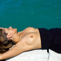 Topless With Long Brown Hair Laying On Seawall By Water - Brown Hair, Hard Nipple, Long Hair, Topless
