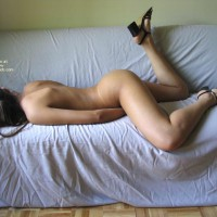 Nude Girl Lying On A Sofa - Black Hair, Leg Up, Sandals